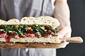 A flatbread sandwich with two different types of hummus, beetroot and parsley