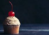A cupcake with peanut frosting and a cocktail cherry in front of a dark background