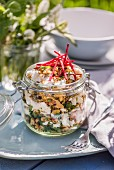 Rice salad with nuts, seeds, feta, coriander and mint in a screw-top jar