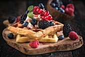 Belgian waffles with ice cream and berries on a wooden board