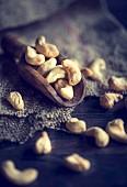 An arrangement of cashew nuts on a wooden scoop