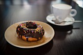 Chocolate donut with sprinkles and coffee