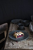 A piece of blackberry tart with cottage cheese on a plate, on a rustic wooden table