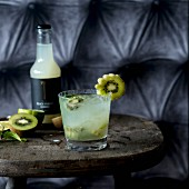 A glass of kiwi lemonade on a rustic wooden stool