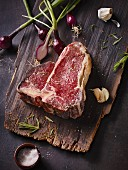 A raw, dry-aged T-bone steak on a wooden board