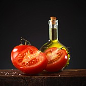 Fresh tomatoes in front of a bottle of olive oil
