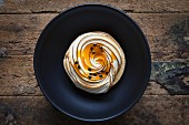 A passion fruit ad lemon meringue tart on a black bowl with a wooden background