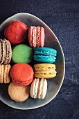 Sweet and colorful macaroon cookies in the plate on dark background