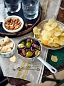 Various snacks (olives, potato chips, Parmesan, almonds)