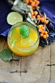 Sea buckthorn juice with slices of lime and lemon balm