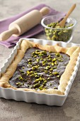 Chocolate tart with pistachios in a square-shaped baking dish