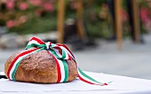 A loaf of bread wrapped with red, white and green ribbon