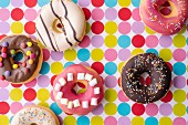 Colourful decorated donuts on a dotted tablecloth (top view)