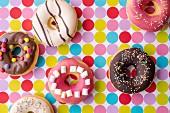 Bunt verzierte Donuts auf gepunkteter Tischdecke (Aufsicht)