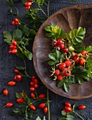 Rosehips in and around a wooden bowl