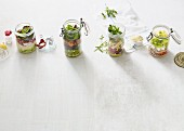 Four different salads in glass jars