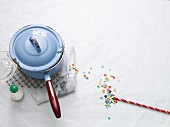 A pan with handle and a straw with confetti