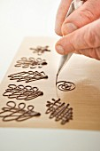 Piping chocolate decorations on baking paper
