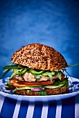 A chicken burger with avocado and rocket