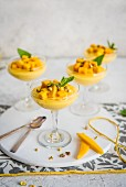 Mango mousse in stem glasses with mango chunks, pistachio nuts and fresh mint
