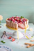 Raspberry and strawberry charlotte on a cake stand, slice removed