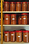 Jars of crushed chilli peppers in a Benedictine monastery near Siena, Tuscany, Italy