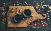 Chinesischer schwarzer Tee in Teeschalen auf Holzbrett