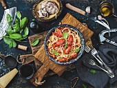 Italian style pasta dinner. Spaghetti with tomato and basil in plate on wooden board and ingredients for cooking pasta
