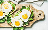 Healthy breakfast sandwiches. Bread toasts with fried eggs and fresh vegetables on rustic wooden board
