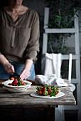 Frau schneidet Erdbeeren an Tisch in rustikaler Landhausküche