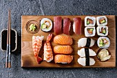 Nigiri and maki sushi rolls on a wooden serving board with soy sauce and chopsticks