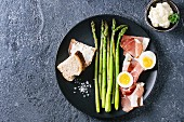 Green asparagus with egg, bread and ham bacon on a black plate (seen from above)