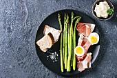 Grüner Spargel mit Ei, Brot und Schinkenspeck auf schwarzem Teller (Aufsicht)