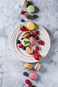 Variety of colorful french sweet dessert macarons with different fillings served on white vintage plate with spring flowers and berries