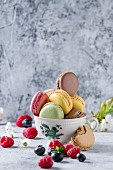 Variety of colorful french sweet dessert macarons with different fillings served in vintage tea cup with spring flowers and fresh berries