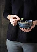 Person hält Keramikschälchen und ein Basilikumblatt in den Händen