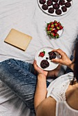 A woman with jeans sitting and eating cookies and fresh strawberries
