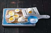 Sliced hard boiled eggs with an egg slicer and a bowl of salt on a wooden board