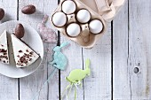Two pieces of Easter cake with chocolate eggs, Easter rabbits, and an egg carton