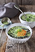 Pea soup with cheese crisps and black sesame seeds