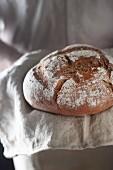A fresh loaf of crusty bread on a linen cloth