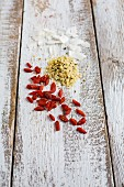 Goji berries, hemp seeds and coconut chips on a wooden background