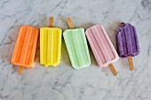 Five different coloured ice lollies on a marble background
