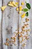 Ananas, Mango, Spinat, Knuspermüsli und Mandelstifte auf Holzuntergrund
