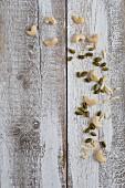 Mandelstifte, Cashewnüsse und Pistazien auf Holzuntergrund (Aufsicht)