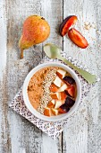 A smoothie bowl with buckwheat groats, plum, orange, pear and sesame seeds