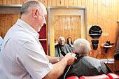 Man with dementia having his hair cut