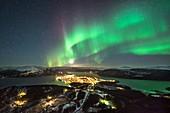 Aurora borealis over city lights