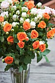 Mixed cut roses (Rosa sp.) in a vase
