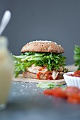 A gourmet chicken burger with mayonnaise and tomatoes